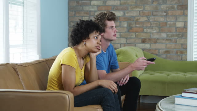 young woman acting bored while her date watches tv