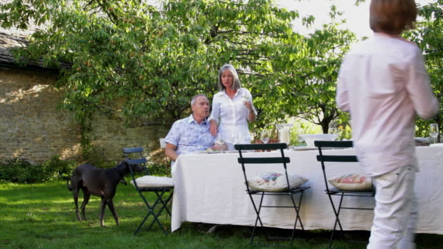 WS Young woman and boy (12-13) joins in parents at table in garden / London, United Kingdom
