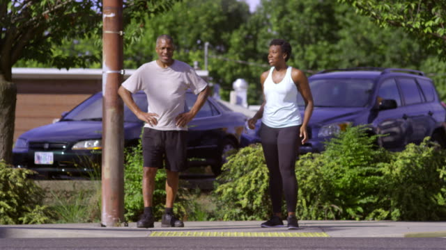Young woman and Dad wait for street crossing.