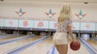 MS Young Woman and man throwing bowling ball in bowling alley and giving high five