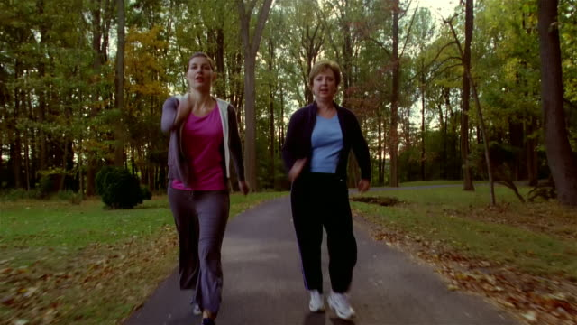 Young woman and mature woman power walking on park footpath