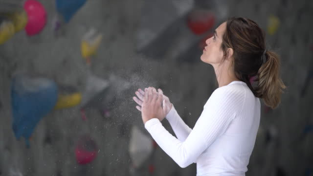 MS Young woman applying chalk on her hands before she climbs
