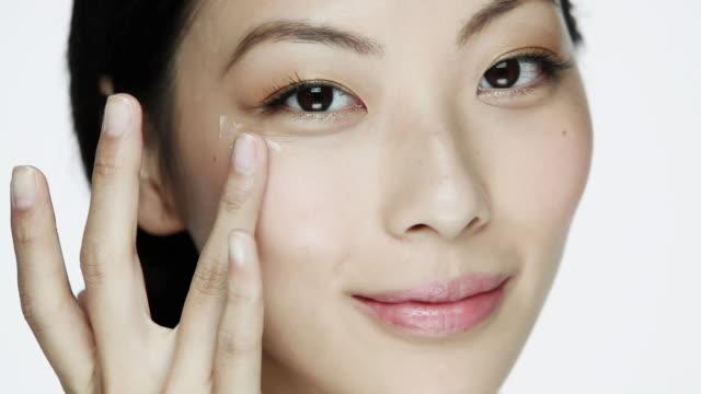 Young woman applying eye cream