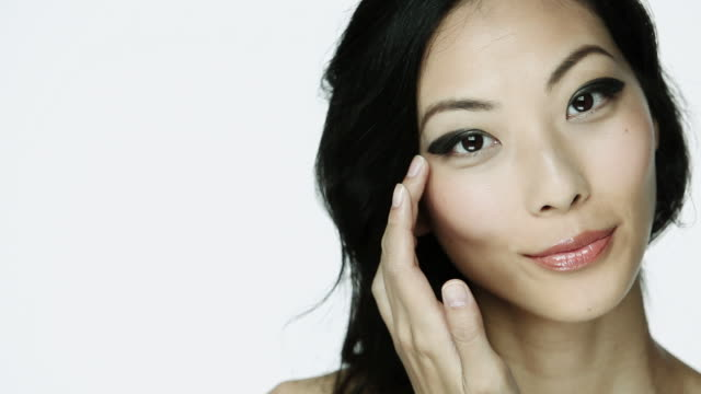 Young woman applying eyeshadow
