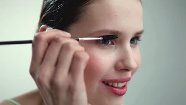 CU Young woman applying mascara / London, UK