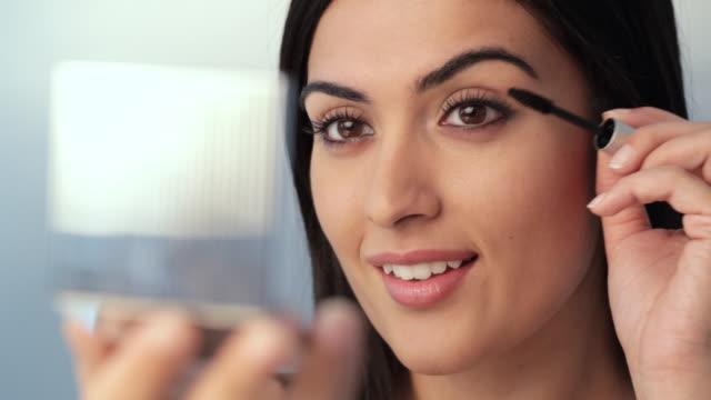 CU Young woman applying mascara to eyelashes / Singapore
