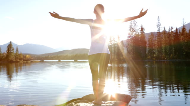 Ung kvinna armarna utsträckta vid sjön