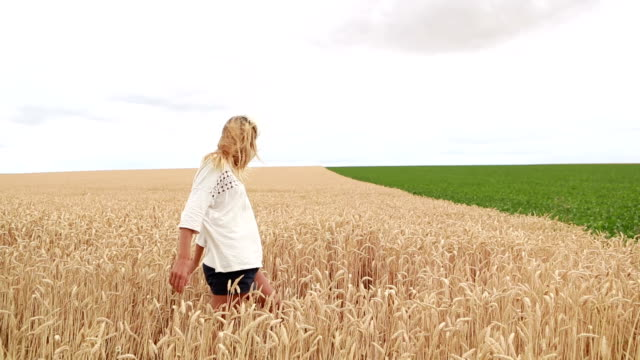 Young woman arms outstretched in wheat field