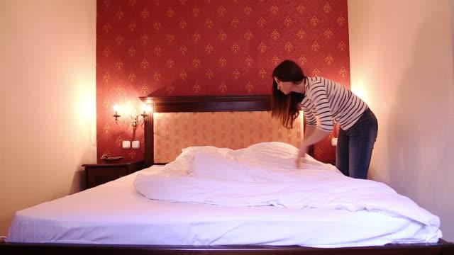 Ung kvinna att ordna sängen.