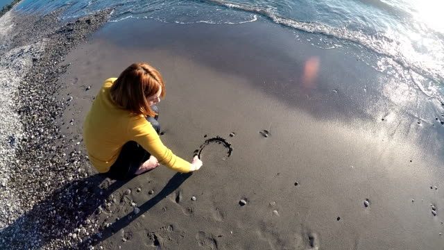 Young woman at 30s drawing a broken heart shape at the beach