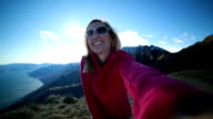 Young woman at top of mountain taking a selfie