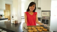 MS Young woman baking cookies at home.