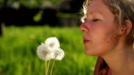 SLOW MOTION: Young woman blowing a dandelion