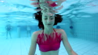 Young woman blowing air bubbles underwater