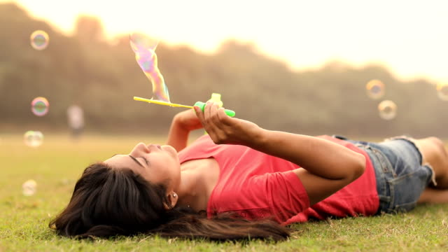 Young woman blowing bubbles in the park, Delhi, India