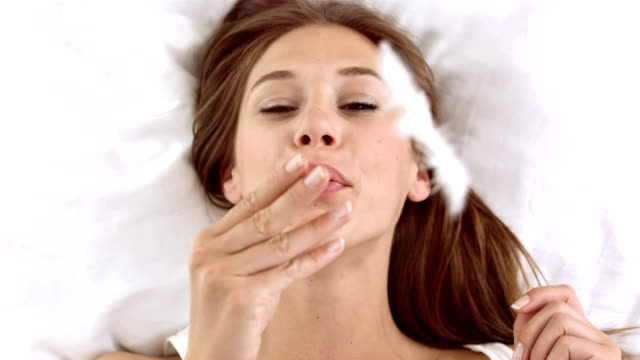 HD: Young Woman Blowing Feather In Bed