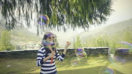 Young woman blowing soap bubbles in outdoor.