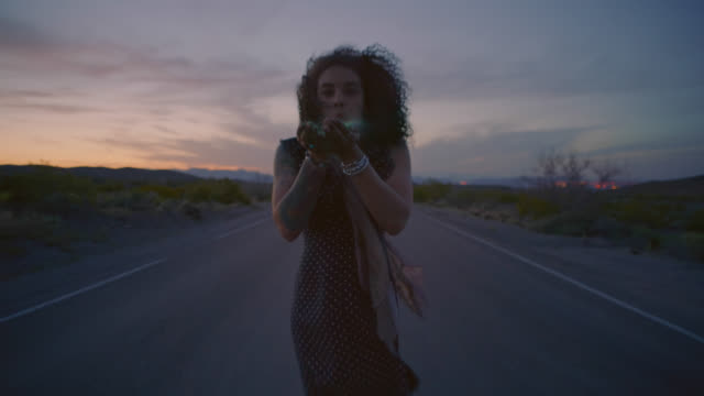 Young woman blows green sand into the wind on empty desert highway at sunset.