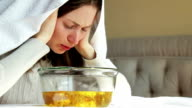 young woman breathes herbal decoction