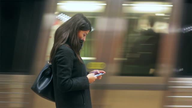 Junge Frau, die Ihr smartphone suchen in der U-Bahn-station entfernt.