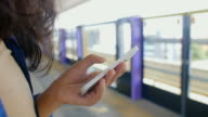 Young woman browsing her smartphone on station