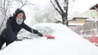 Young woman brushing away the snow from the car.
