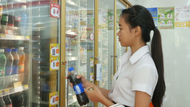 Young woman buying refrigerated groceries product in refrigerated section