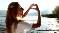 Young woman by the lake making a heart shape with her hands