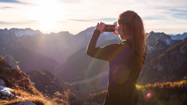 Jonge vrouw vastleggen van herinneringen met haar smartphone van een berg