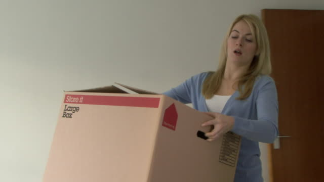 Young woman carrying a box into room and opening, looking fretful, UK