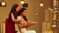 Young woman celebrating diwali festival with her daughter