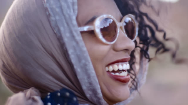 CU. Young woman channeling retro movie starlet in vintage shawl and sunglasses talks and laughs at camera.