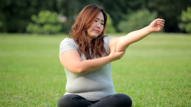 Young woman checking her arm fat