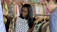 MS A Young Woman chooses between dresses in a vintage clothing store