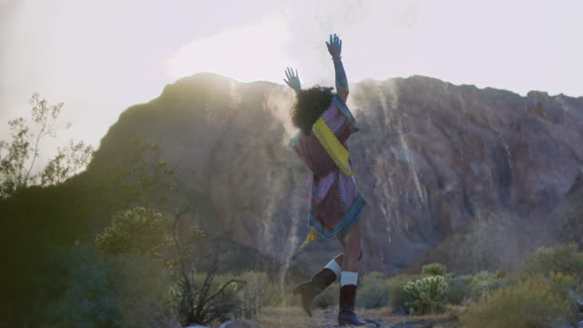SLO MO. Young woman claps her hands and dances in a circle in a cloud of colorful sand in scenic desert.