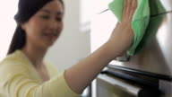 CU SELECTIVE FOCUS Young woman cleaning oven door, focus on hand / China