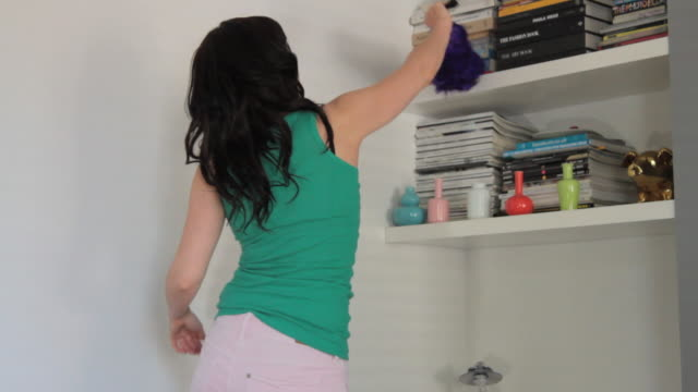 MS Young woman cleaning shelves, singing and dancing with duster / London, United Kingdom