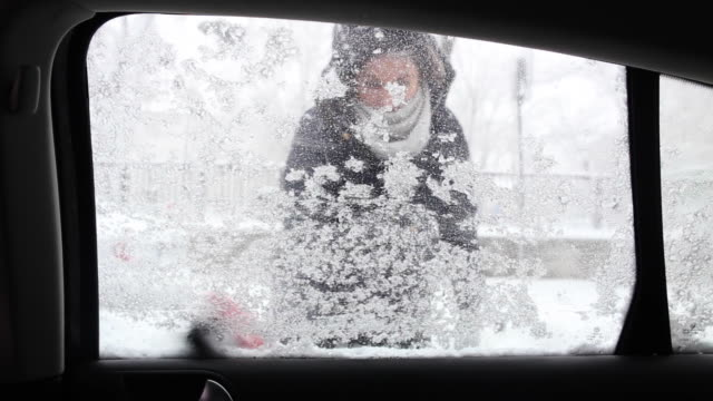 Young woman cleaning the ice from the car with the brush.