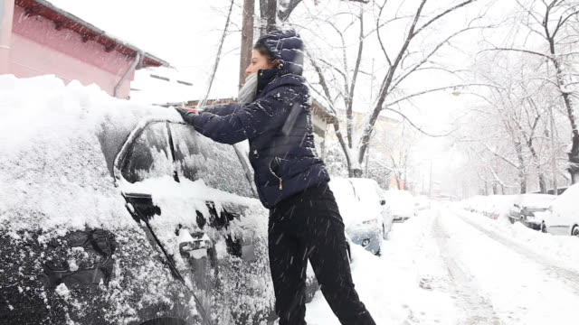 Young woman cleaning the snow from a car.