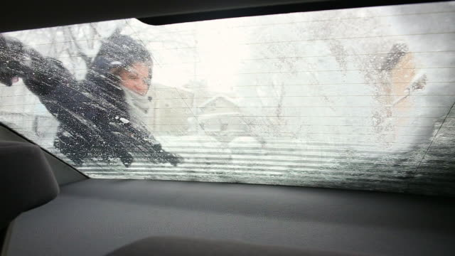 Young woman cleaning the snow from the rear window of the car.