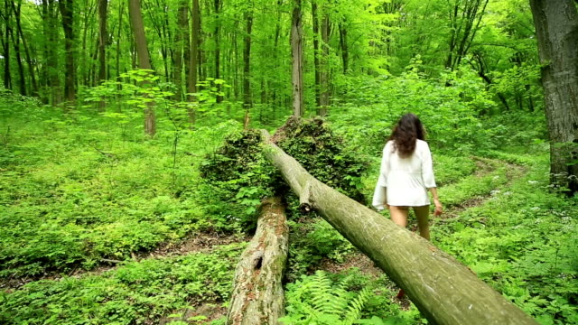 Young woman climbs over a log