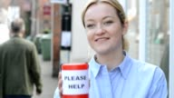Young woman collects charity donation from man in the street