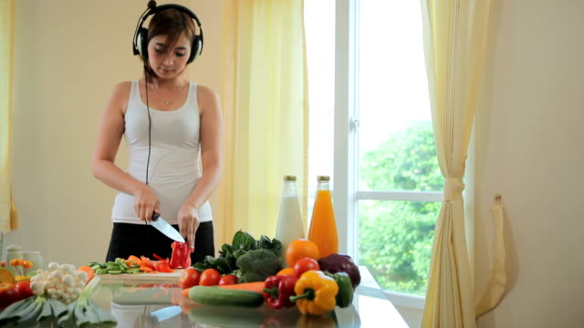 Young woman cooking in kitchen and listen music