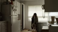 WS Young woman covered with blanket entering kitchen and removing milk from refrigerator / Provo, Utah, USA