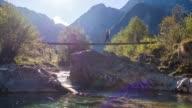 Junge Frau, die über eine Hängebrücke über einen Gebirgsbach
