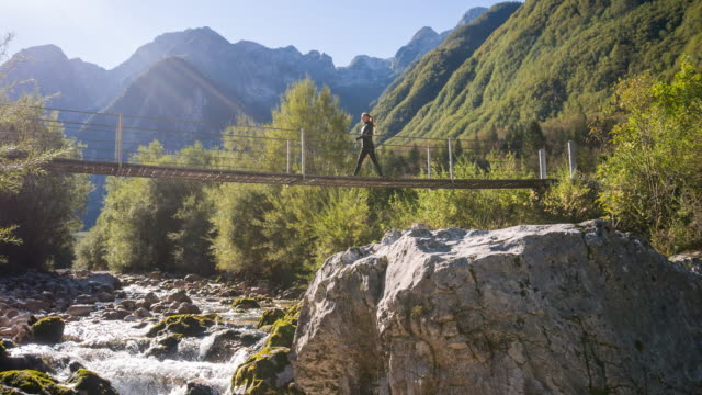 Young woman crossing a suspension bridge over mountain stream