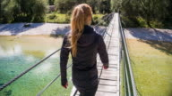 Young woman crossing a wooden suspension bridge over a stream