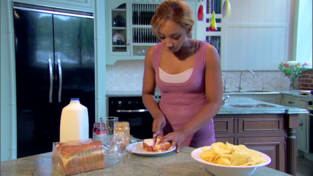 A young woman cuts her peanut butter and jelly sandwich and picks up one half.