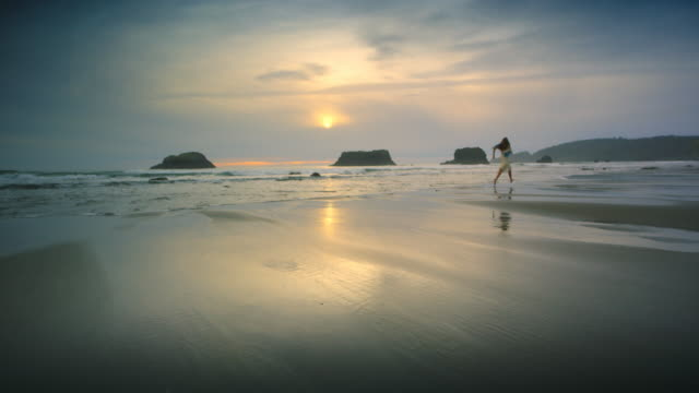 Young woman dancing and leaping on Ocean Beach at Sunset