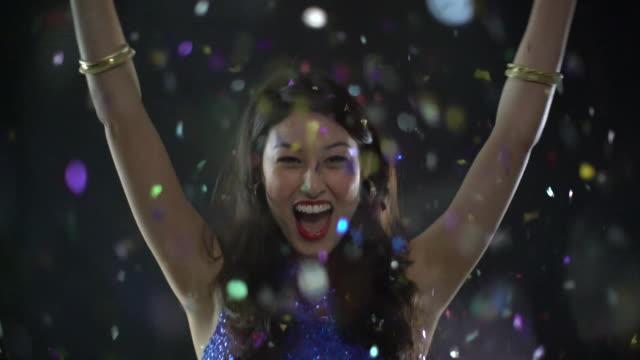 MS SM young woman dancing as confetti falls.